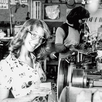 Janet Deering sanding a pot on a spinning lathe